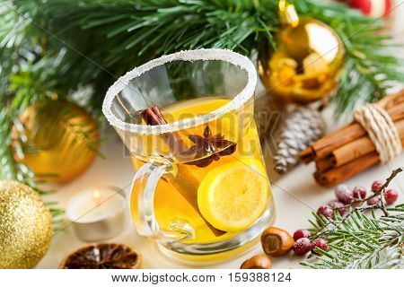 Holiday winter hot citrus drink near Christmas tree with decorations. Lemon tea.