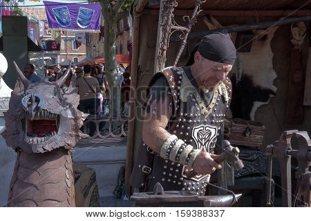 ALCALA DE HENARES, MADRID, SPAIN - OCTOBER 10: blacksmith working outdoors during the recreation of a medieval market. Photo taken on 10 October 2015 in Alcalá de Henares, Madrid, Spain