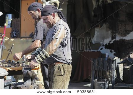 ALCALA DE HENARES MADRID SPAIN - OCTOBER 10: blacksmith working outdoors during the recreation of a medieval market. Photo taken on 10 October 2016 in Alcalá de Henares Madrid Spain