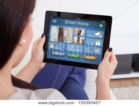 Close-up Of Woman Using Smart Home System On Digital Tablet At Home