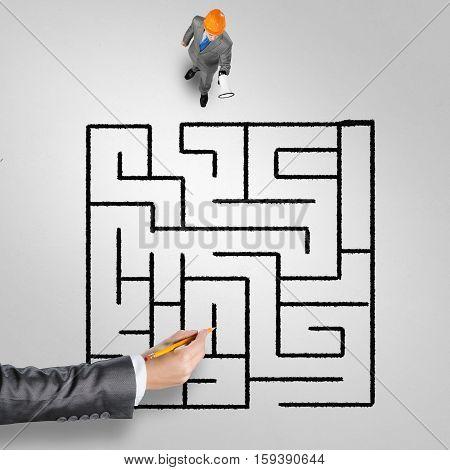 Top view of businessman in helmet with loudspeaker against maze drawn on floor