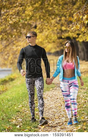 Beautiful Young Couple Walking Together In The Park. Autumn Environment.