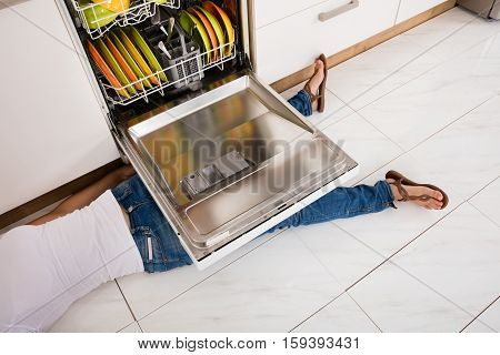 Close-up Of Young Woman Leg Lying Under A Dishwasher In Kitchen