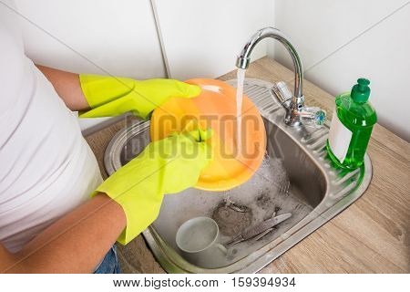 Close-up Of Person Hand Washing Plate In The Sink At Home