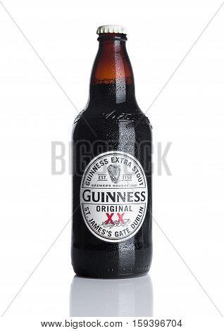 LONDON UK - NOVEMBER 29 2016: Guinness extra stout beer bottle on white background. Guinness beer has been produced since 1759 in Dublin Ireland.