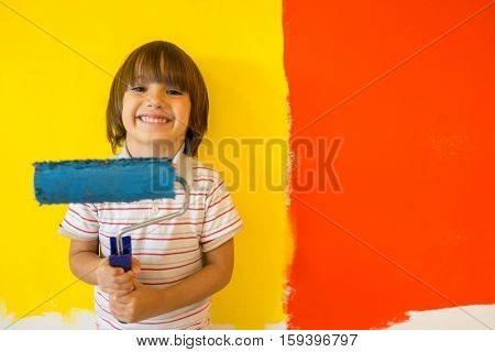 Child painting the home wall in colors