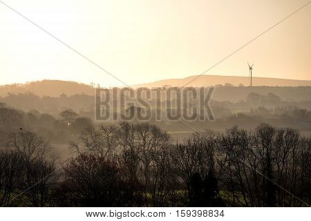 Rural view at sunrise showing wind turbine