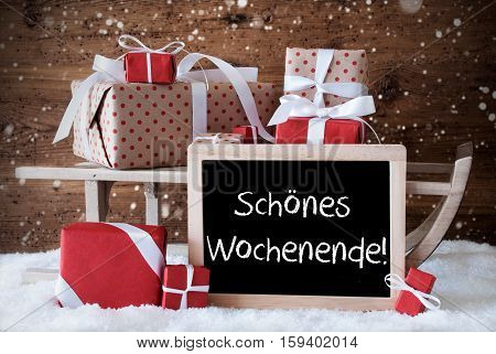 Chalkboard With German Text Schoenes Wochenende Means Happy Weekend. Sled With Christmas And Winter Decoration And Snowflakes. Gifts And Presents On Snow With Wooden Background.