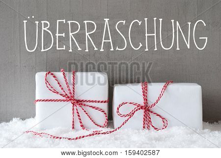 German Text Ueberraschung Means Surprise. Two White Christmas Gifts Or Presents On Snow. Cement Wall As Background. Modern And Urban Style.