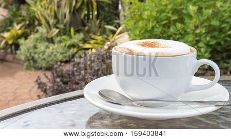 Closeup A cup of hot cappuccino on glass table with garden nature background