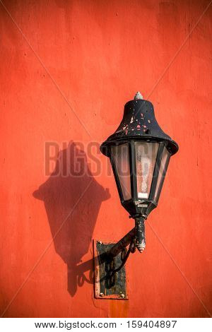 Red Wall And Black Street Light