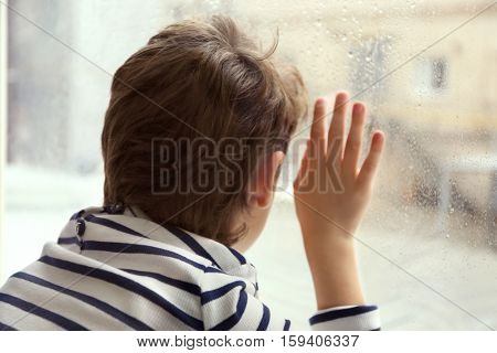 Close up view of little boy looking out of window