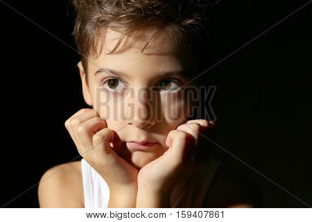 Cute little boy on black background, close up view