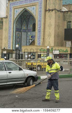 Tehran Province- IRAN-December 1 2016 A Portrait of An Urban Street Cleaner Man Holding Hand-made Sweeping Tool By Gloved Hand in Front of Mosque Building