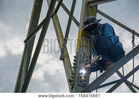 Welder work at high Electric high voltage pole 230 Kv