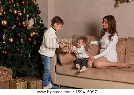 Happy family with  gift boxes are sitting on a sofa near Christmas tree at home. Merry Christmas and Happy New Year. Beautiful young mother with two sons.
