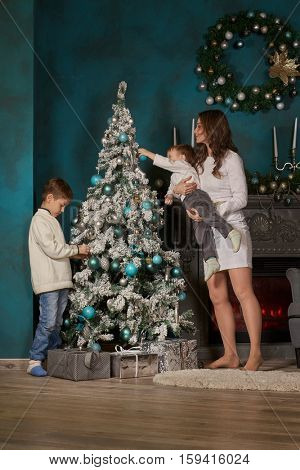 Happy family are decorating a Christmas tree in the house.  Merry Christmas and Happy New Year. Beautiful young mother with two sons.