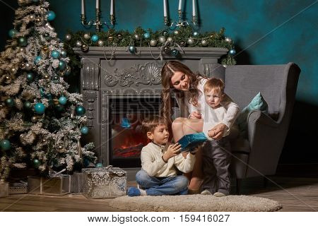 Happy family with  gift box sitting near Christmas tree at home. Merry Christmas and Happy New Year. Beautiful young mother with two sons.