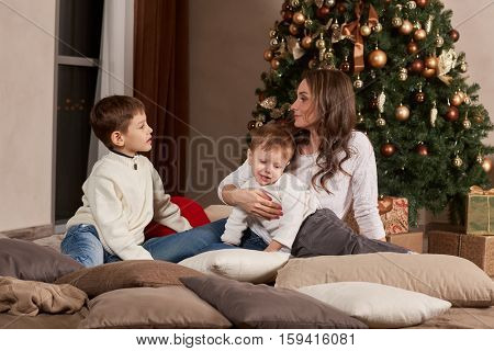 Happy family are sitting on a  bed near Christmas tree at home. Merry Christmas and Happy New Year. Beautiful young mother with two sons.