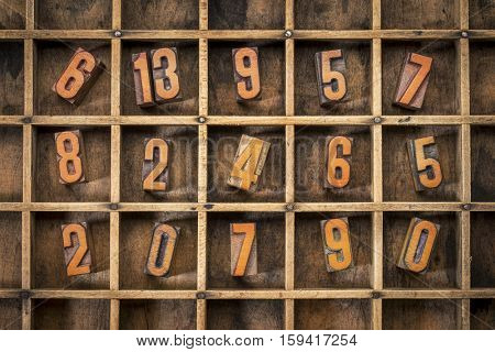 random letterpress numbers stained by black ink in old typesetter case with dividers