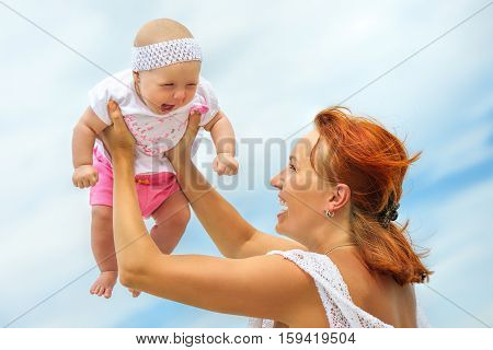 Beautiful Mother And Baby outdoors. Beauty Mum and her Child playing in outdoor together. Outdoor Portrait of happy family.