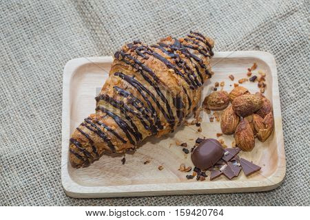 Closeup Croissants on a wooden plate. chocolate and almonds. Focus on Croissant. The background is blurred out of focus at some point.