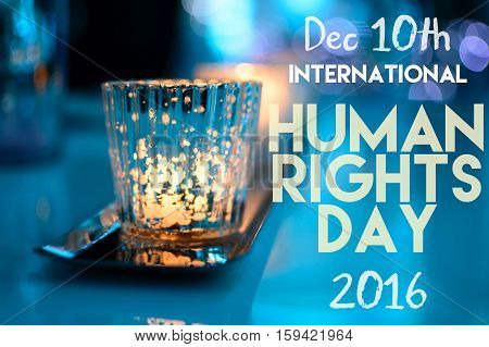 International Human Rights Day 2016 social image with bright candlelight and blue background and words December 10th written in copy for card, postcard,communication or message. Part of a human rights conceptual image series.