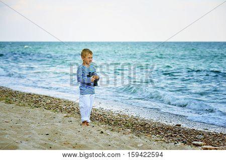 The little boy with binoculars , walking the coast