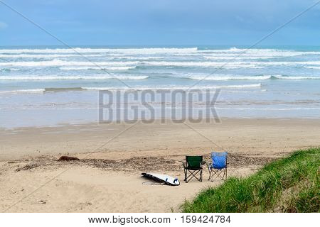 Surfing board and couple of chairs at the beach South Australia