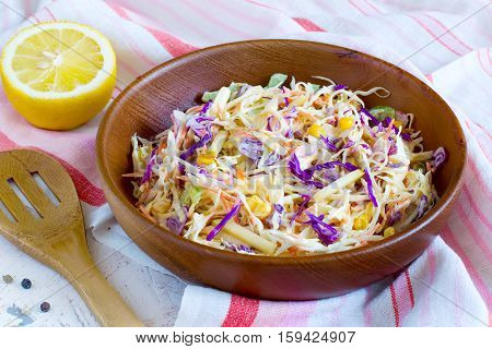 Salad coleslaw in a wooden bowl close-up rustic style.