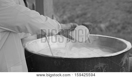 Cheesemaker Pour Rennet Into The Warm Copper Cauldron To Produce