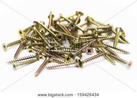 Heap of wood screws closeup on white background.