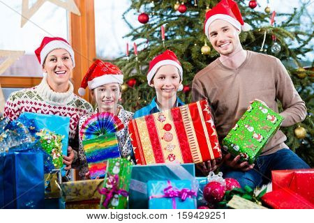 Mum, dad and sons on X-mas during handing out of presents under Christmas tree