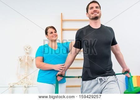 Young man working out with physiotherapist and resistance band