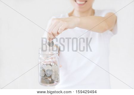business finance saving banking and people concept - close up of woman hands putting us dollar money into glass mason jar