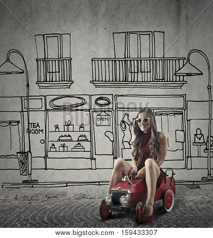 Girl sitting on a red toy car and playing in an imaginary room
