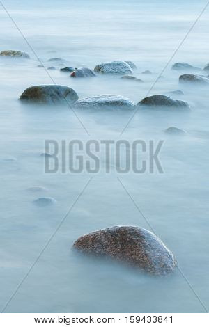 Long exposure of blue sea and stones in the water