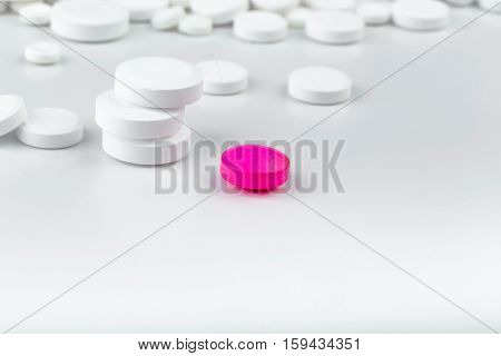 Bunch Of White Tablets. Scattered Pills. Single Pink Pill