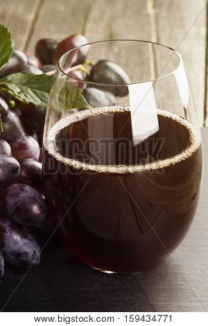 Red Wine And Dark Grapes On A Wooden Background. Toning