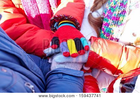 Close-up of children in warm clothing holding hands