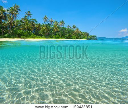 Tropical Island Beach with the half underwater view with sea bed. North Sulawesi Indonesia.