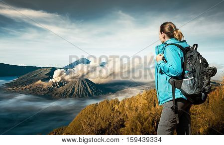 Young woman backpacker enjoying view volcano Bromo island Java Indonesia. Discovering world summer vacation concept.