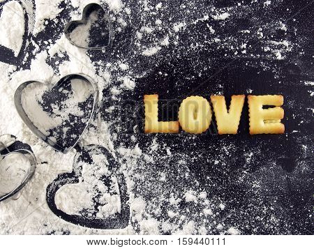 love word, biscuit cookies letters with heart shaped cookie cutter and flour on wood kitchen table