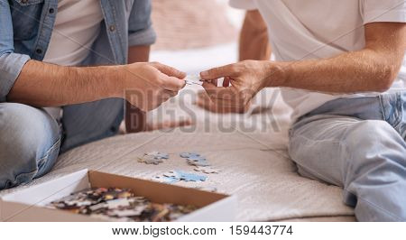 Men gathering pieces of puzzle together. Colorful numerous small puzzle pieces lying in the box and on the bed while being the part of the game of two men