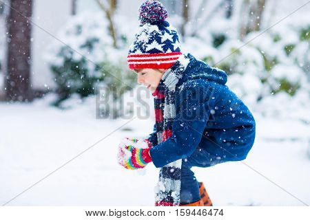 Winter portrait of little kid boy in colorful clothes, outdoors during snowfall. Active outdoors leisure with children in winter on cold snowy days. Happy child having fun with snow