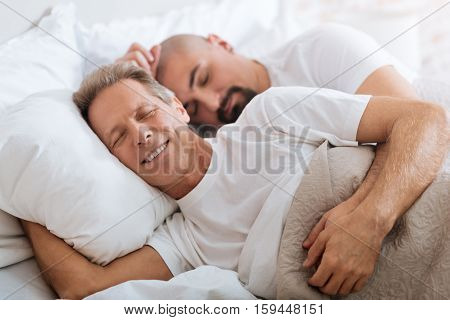 We sleeping together. Cheerful positive happy non-traditional couple lying on the bed in the bedroom while expressing happiness and sleeping