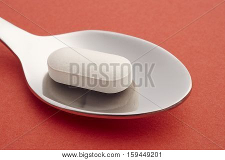 Pill and spoon detail. Red background. Medicament treatment. Health care photo