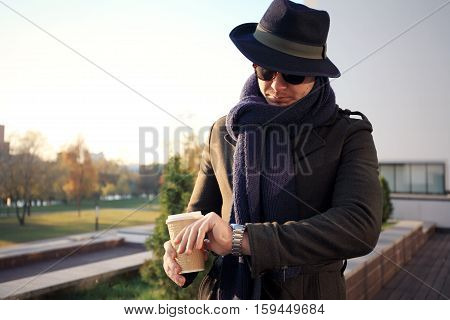 Trendy handsome young man in autumn fashion standing in urban environment