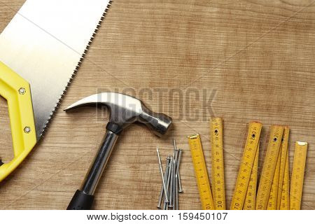 Hammer, nails, ruler and saw on wood. Copy space