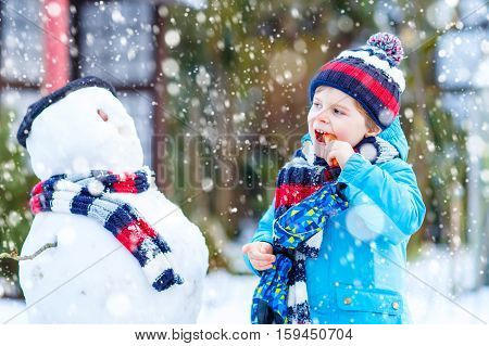 Funny little kid boy making a snowman and eating carrot, playing and having fun with snow, outdoors  on cold day. Active leisure with children in winter.